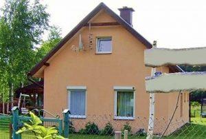na zdjęciu widok z ulicy na dom do sprzedaży nad jeziorem